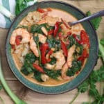 Bowl of shrimp curry topped with spinach and red pepper, spoon in bowl.
