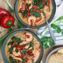 Two green bowls containing shrimp curry topped with spinach and red pepper, onions and peppers on table.