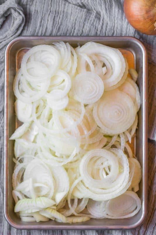 Sliced onions on a half sheet pan.