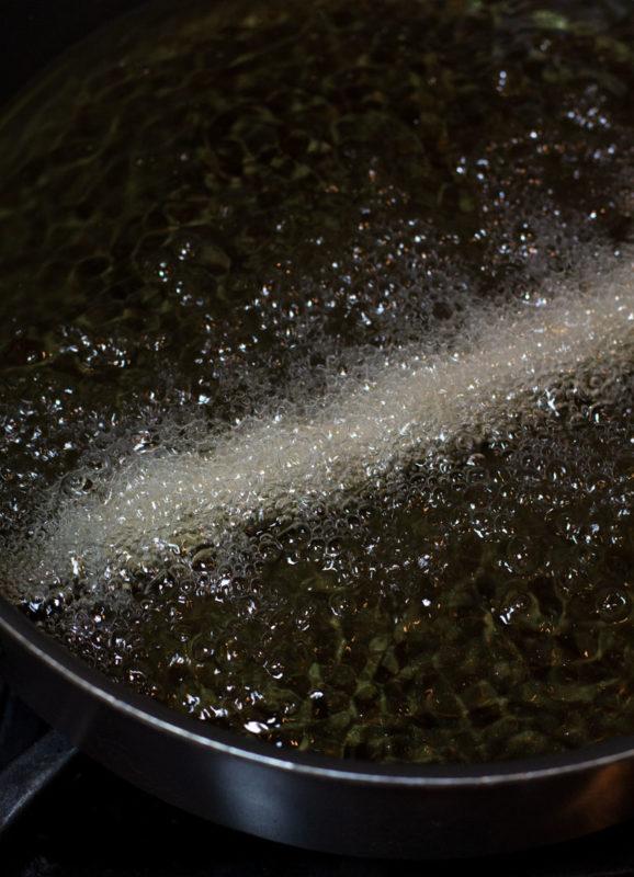 Deep frying cinnamon twist churros in canola oil.
