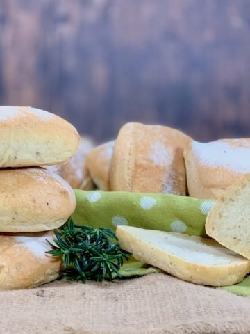 stack of herb sourdough ciabatta rolls with one slice