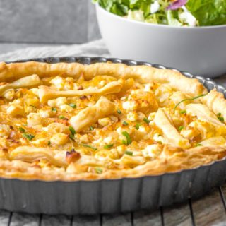 caramelized onion and goat cheese tart in pan with salad behind it