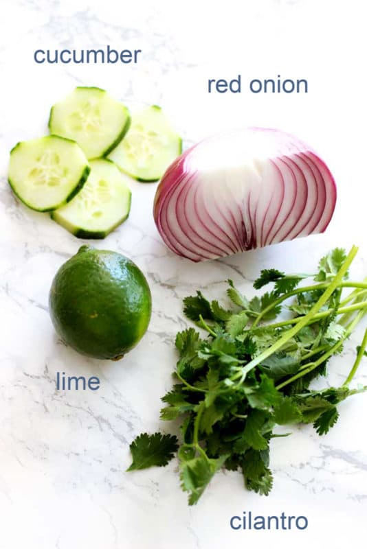 A plate of food, with cucumber, onion, lime, and cilantro.