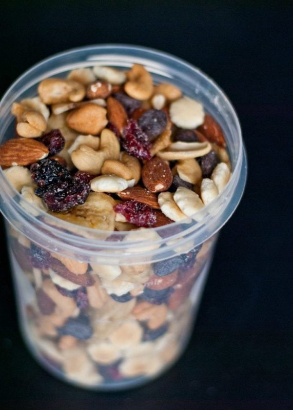 a glass filled with a mix of nuts and raisins
