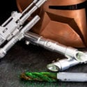 Green lightsaber churro on a table next to a Star Wars helmet and guns.