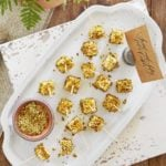 Cubes of feta cheese skewered coated in pistachios on a white plate
