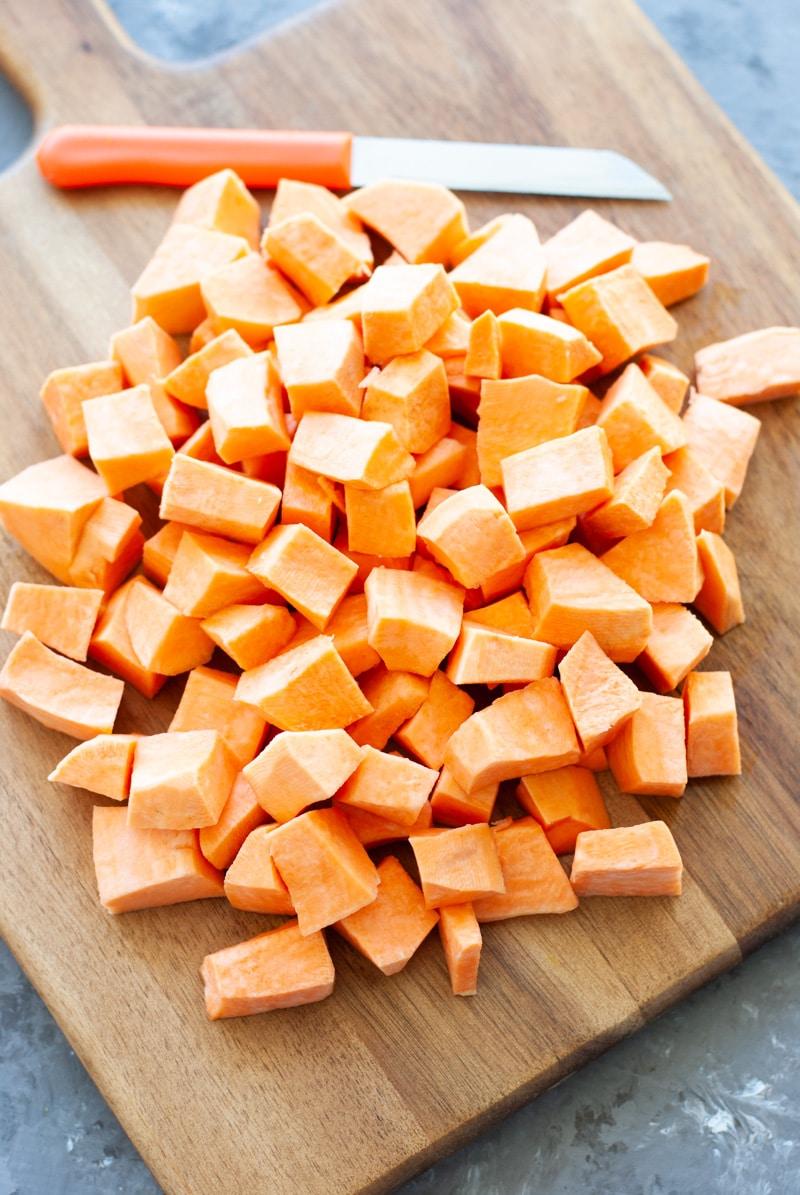 cubed sweet potato on wooden platter.