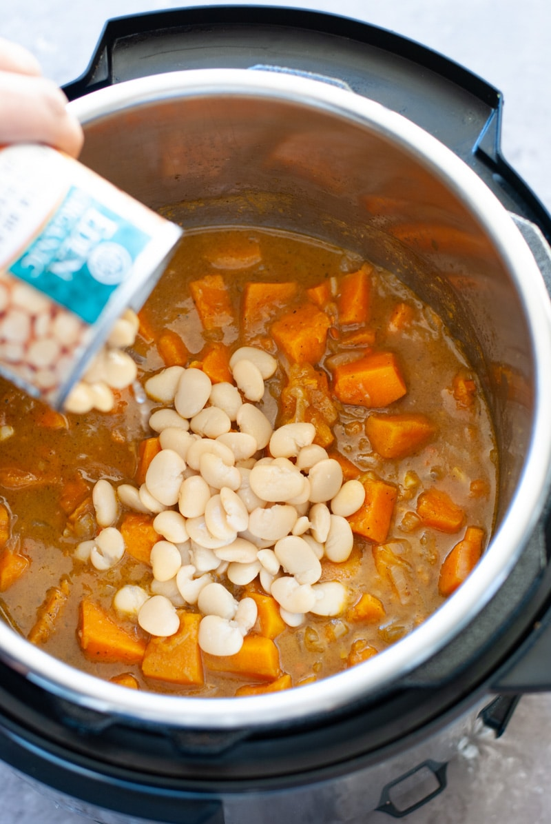 Can of butter beans being poured into sweet potato soup.