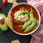 White bowl containing tortilla soup topped with shredded cheese, avocado and cilantro.