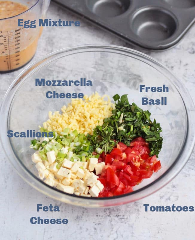 Egg mixture,cheese,basil, scallions, and tomatoes in a bowl on counter.