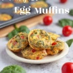 5 mini egg muffins on a plate, spinach and eggs on table.