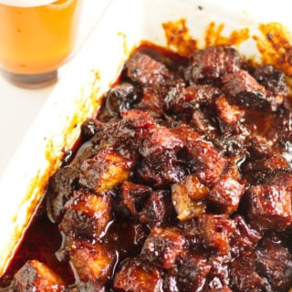 White dish with smoked brisket burnt ends in a kansas city-barbecue sauce with a glass of beer