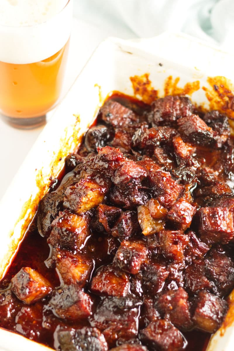 Smoked brisket burnt ends in a white dish covered in BBQ sauce.