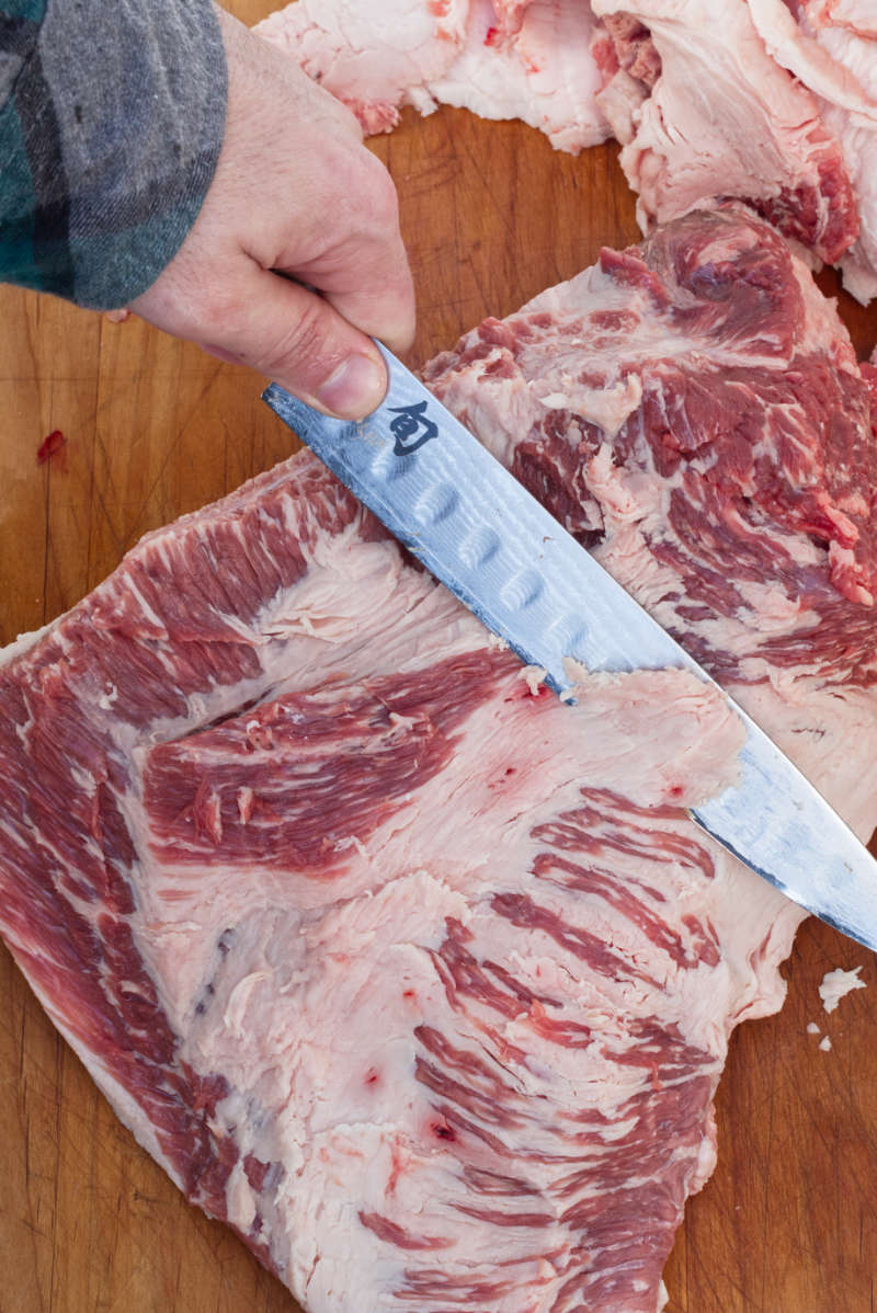 Trimming the hard white fat from a brisket with a boning knife on top of a wooden cutting board