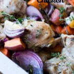 White dish with oven baked chicken and vegetables topped with thyme.
