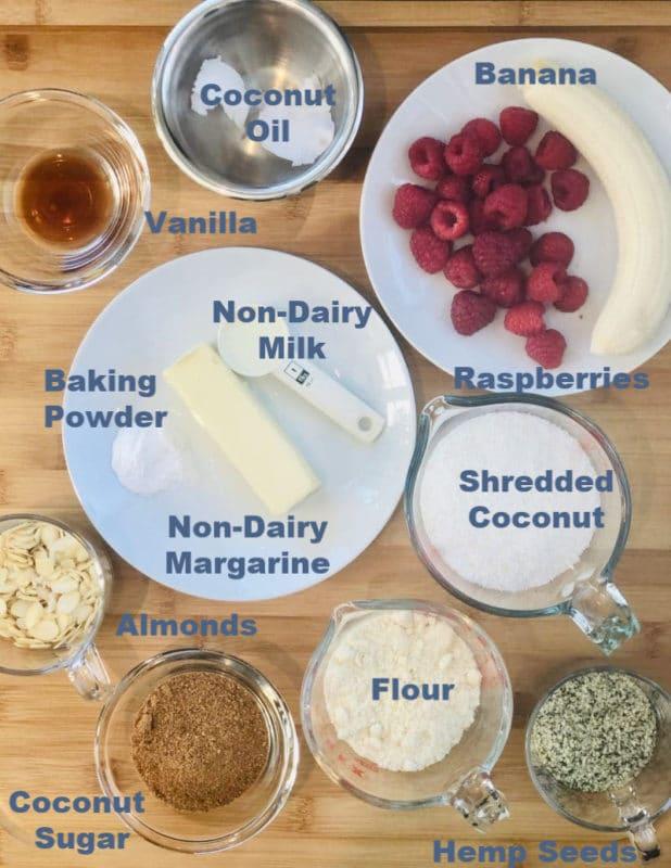 Banana, flour, coconut sugar, shredded coconut, vanilla, non-dairy milk and margarine on a counter.