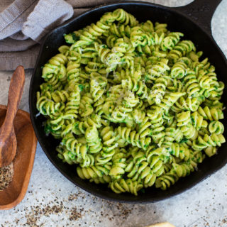 Skillet containing pasta with avocado sauce, Parmesan and pepper on table.