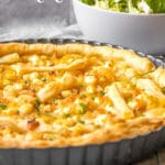 Caramelized onion and goat cheese tart in pan with salad on table.