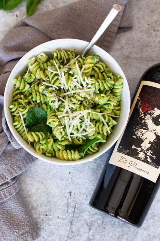 Bottle of Prisoner wine next to a bowl of spinach pasta topped with Parmesan cheese.