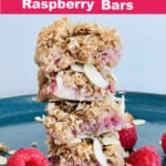 4 raspberry bars stacked on a blue plate, raspberries on plate.