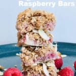 Raspberry bars stacked on a blue plate, raspberries and almonds on plate.