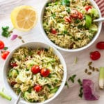 White bowls filled with an orzo salad, lemon, and tomatoes on table.