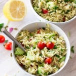 Two white bowls filled with an orzo pasta salad, lemon and tomatoes on table.