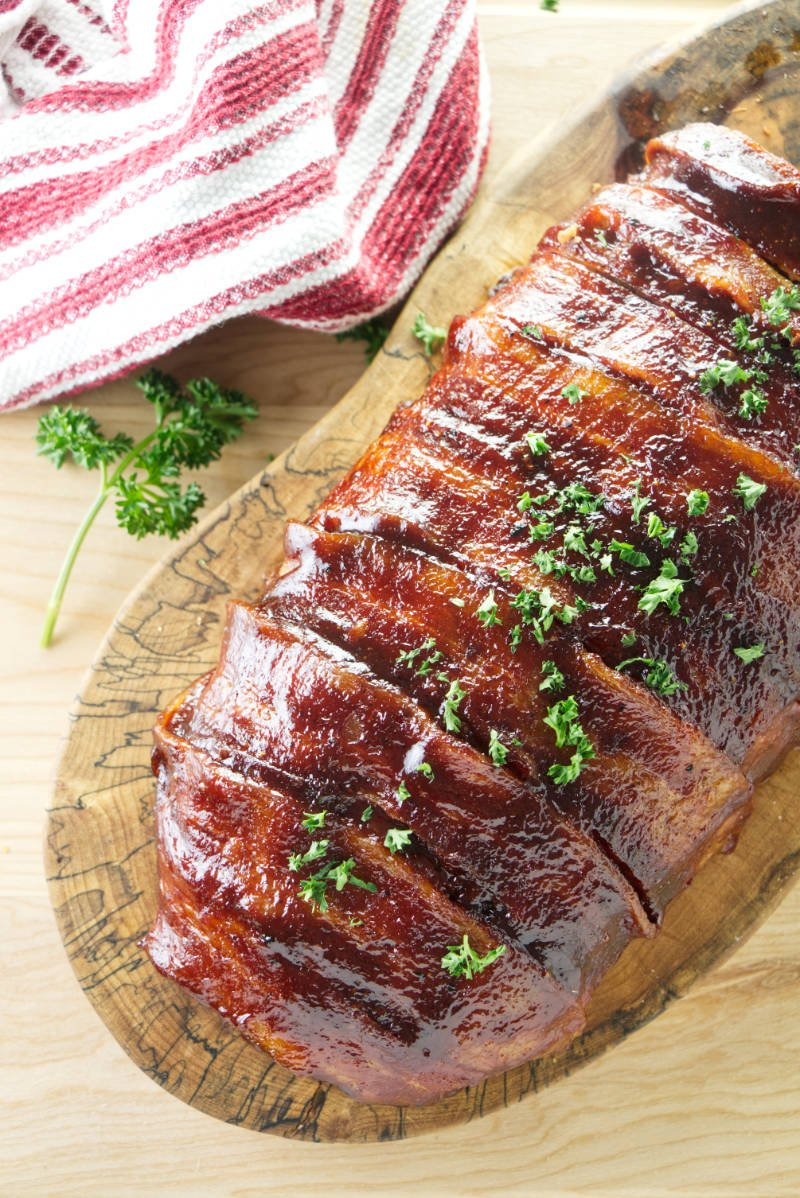 smoked meatloaf wrapped in bacon and brushed with bbq sauce sitting on wood cutting board with red and white towel and parsley
