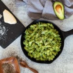 Skillet containing avocado pasta, wine, Parmesan cheese, and pepper on table.