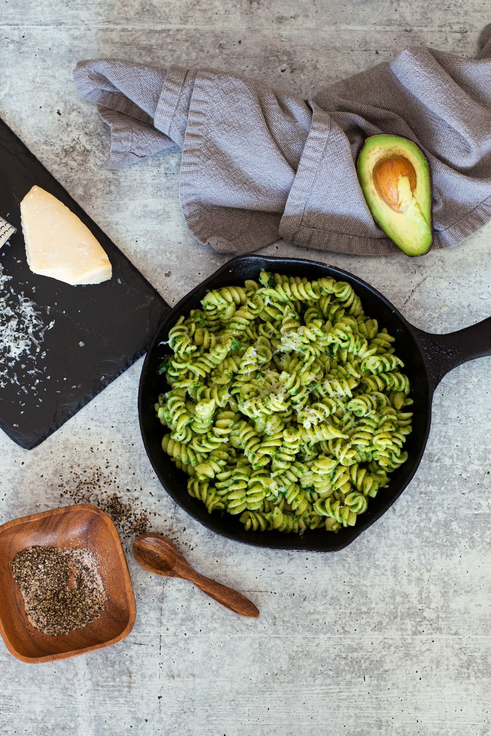 Spinach pasta on a table with Parmesan cheese, avocado on table.