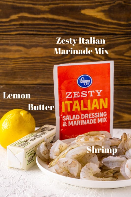 Lemon, butter, shrimp, and Zesty Italian Salad Dressing and Marinade Mix on counter.