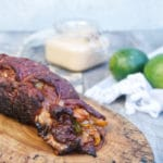 grilled fajita stuffed flank steak with a chipotle lime crema sauce sitting on a wooden background