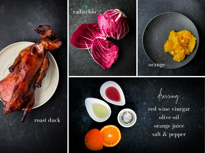 Roasted whole duck, radicchio, orange, red wine vinegar, and orange and spices on a table.