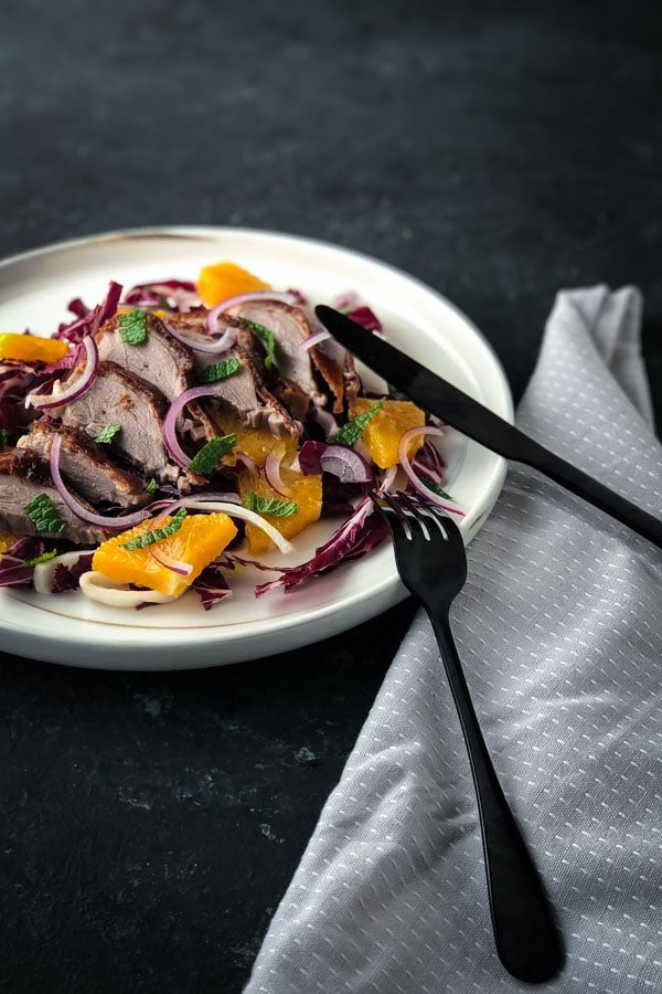 Knife and fork in a plate of radicchio salad, topped with oranges.