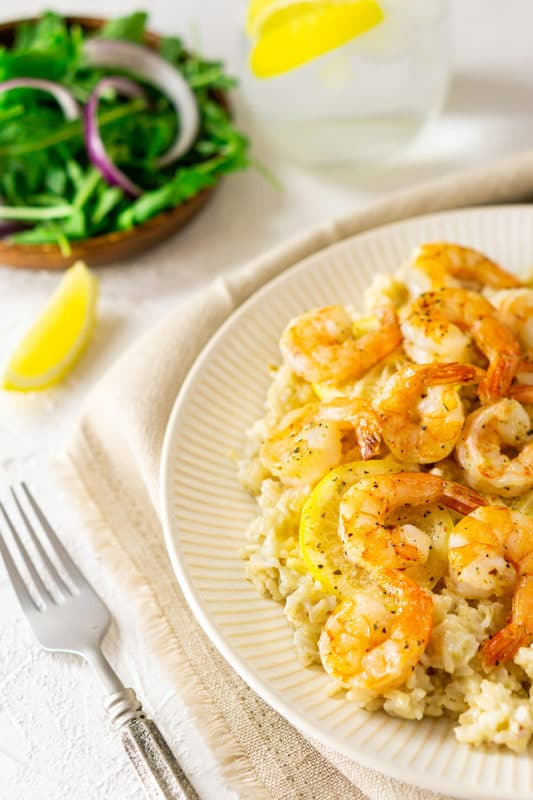Plate filled with shrimp on a bed of brown rice, fork and lemon slices on table.