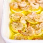 Seasoned shrimp on lemon slices in melted butter in an oven safe dish.