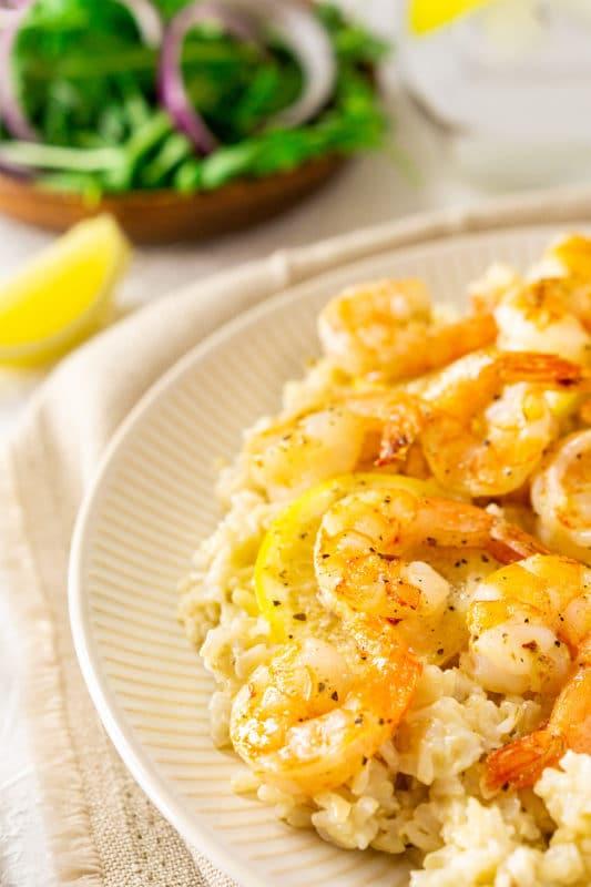 Lemon Butter Shrimp served over a bed of rice, side salad on table.