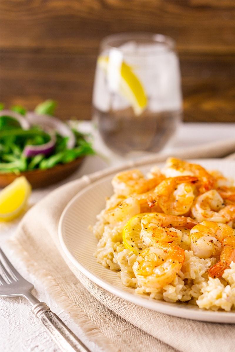 Baked lemon and garlic shrimp served over rice, fork on table.