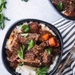 closeup of low-carb braised beef with gravy in a bowl with a striped napkin