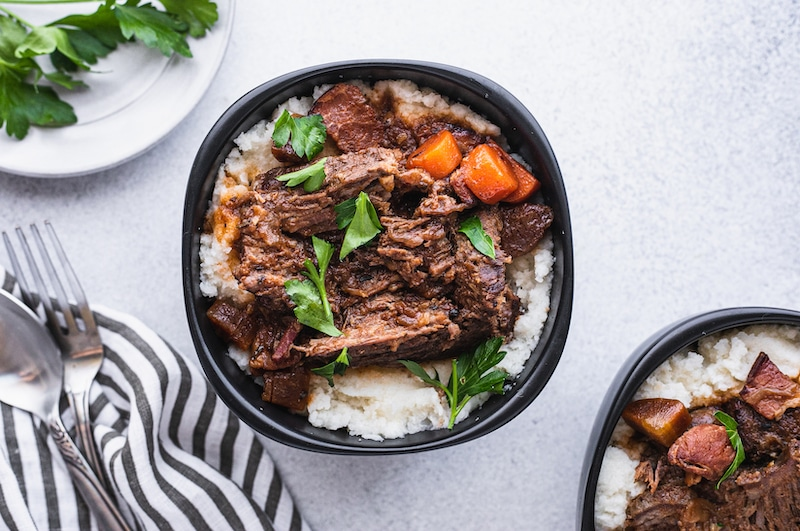 low-carb braised beef with gravy in a bowl with parsley and cauliflower mash