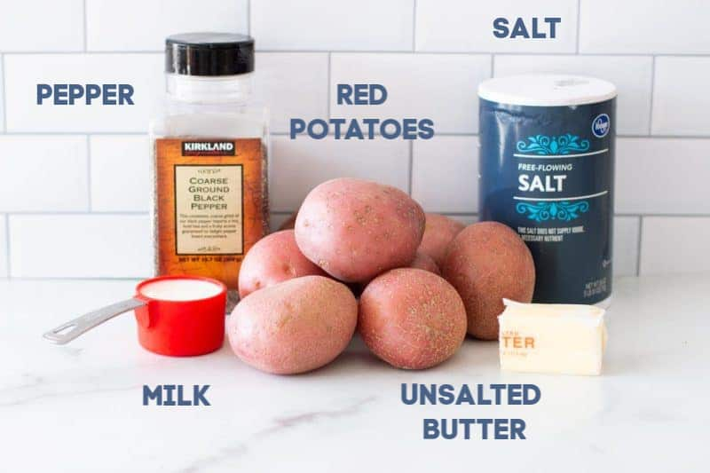 Red potatoes, salt, pepper, milk and butter on a granite counter.