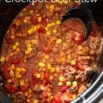 Crockpot filled with southwestern beef stew filled with corn, beans, and tomatoes.