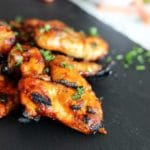 Grilled chicken wings on a black counter top.