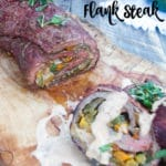 Beef flank steak stuffed with fajita vegetables on a wooden plank