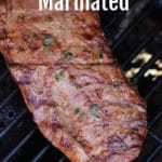 A flank steak on a grill.