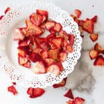 hite plate containing strawberry chips, dried strawberries on counter.