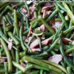 Close up of smoked green beans topped with bacon.
