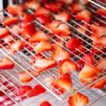 Close up of sliced strawberries on wire food dehydrator trays.