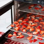 A food dehydrator with trays filled with sliced fresh strawberries.