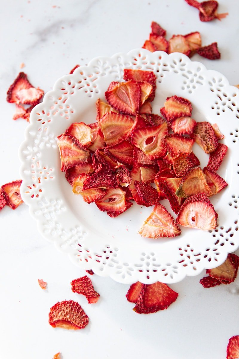 White plate containing strawberry chips, dried strawberries on counter.